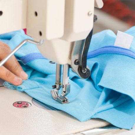 closeup seamstress on the machine sews clothes at a garment factory